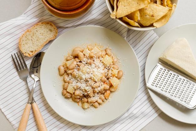 Плоские лежат фасоль и картофель на тарелке