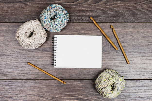 Flat lay of beautiful balls of wool and needles next to a blank notebook for mock up in neutral tones over a wooden table