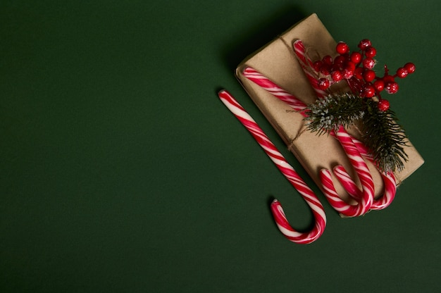 Flat lay of beautiful christmas present in craft wrapping paper decorated with holly and sweet striped white and red lollipops candy canes laid out in the corner of copy space on dark green background