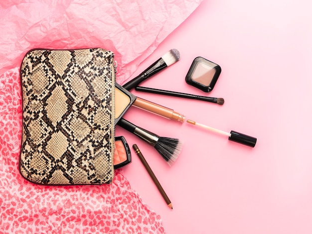Flat lay of beautiful makeup bag with snake design and decorative various cosmetics accessories