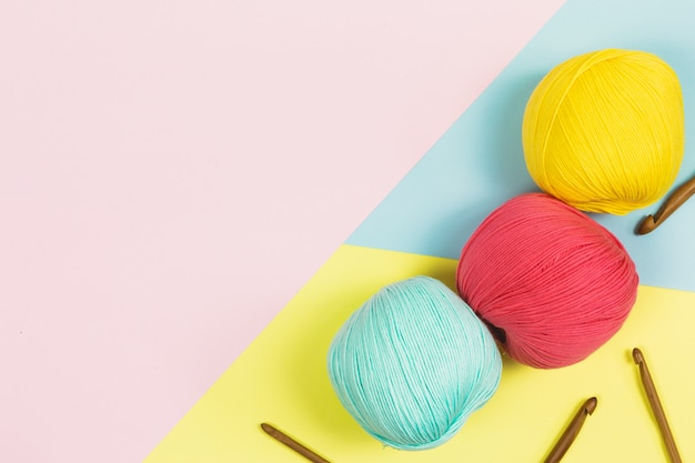 Flat lay of beautiful mint green, coral pink and dark yellow balls of cotton wool next to wooden needles with geometrical pastel colors background