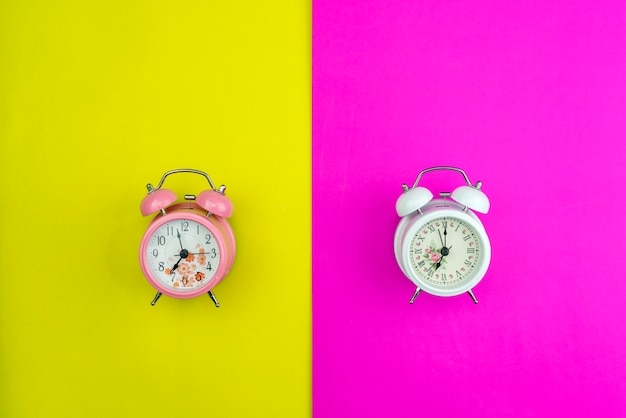 Flat lay of beautiful new alarm clock on pink and yellow paper pastel color background