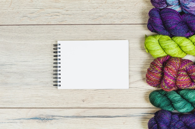 Flat lay of beautiful skeins in purple and green tones and blank notebook for mock up over a wooden table with copy space