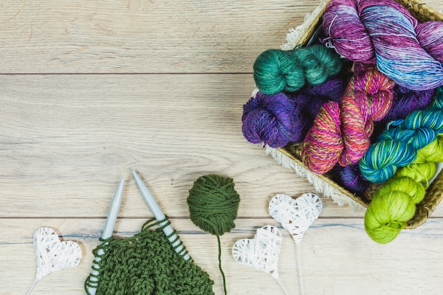 Flat lay of beautiful skeins, white heart decorations and needles in purple and green tones inside a basket over a wooden table