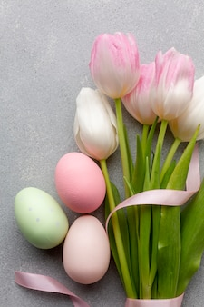 Flat lay of beautiful tulips and colorful easter eggs