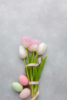 Flat lay of beautiful tulips with ribbon and colorful easter eggs