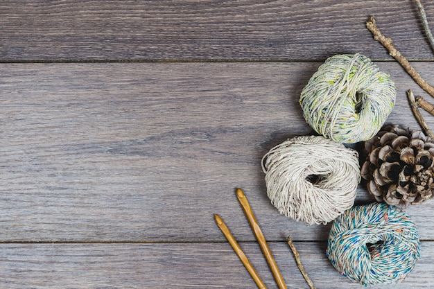 Flat lay of beautiful winter balls of wool, pine corns and needles in neutral tones over a wooden table