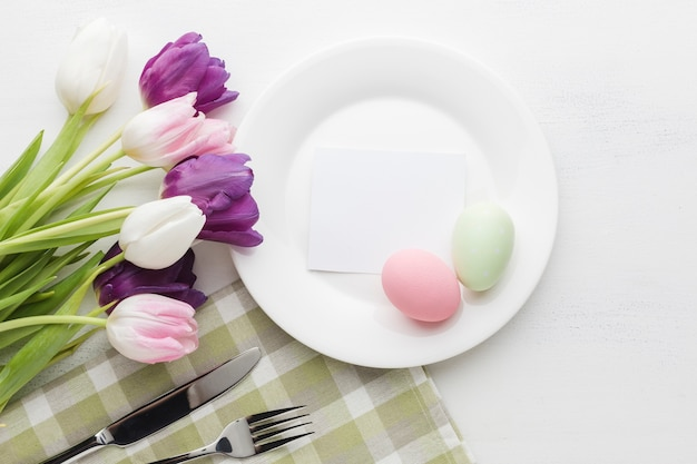 Flat lay of beautifully colored tulips with plate and easter eggs