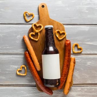 Lay piatto della bottiglia di birra con salatini e salsicce