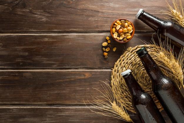 Lay piatto di bottiglie di birra con noci e spazio di copia