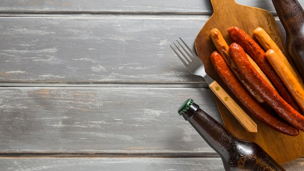 Flat lay of beer bottles with sausages