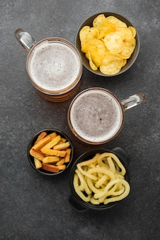Birra piatta laici e snack su sfondo di stucco