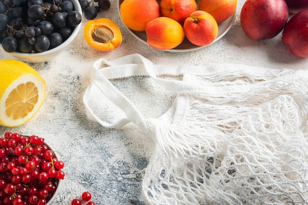 Flat lay, berries, fruits and bag mesh on gray