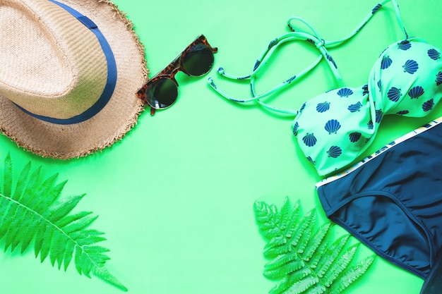 Flat lay of bikini and accessories with fern leaves on green background, summer concept