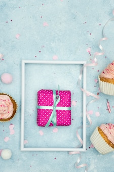 Flat lay of birthday present with cupcakes and ribbon