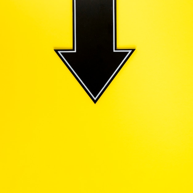 Flat lay black arrow downwards on yellow background with copy-space