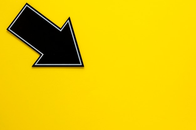 Flat lay black arrow on yellow background with copy-space