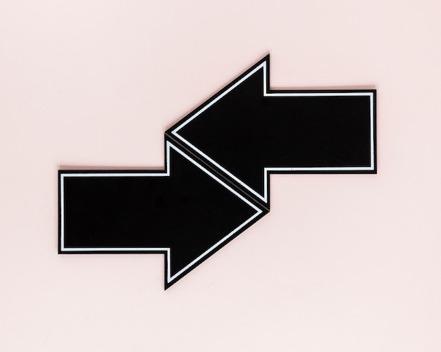 Flat lay black arrows on pink background