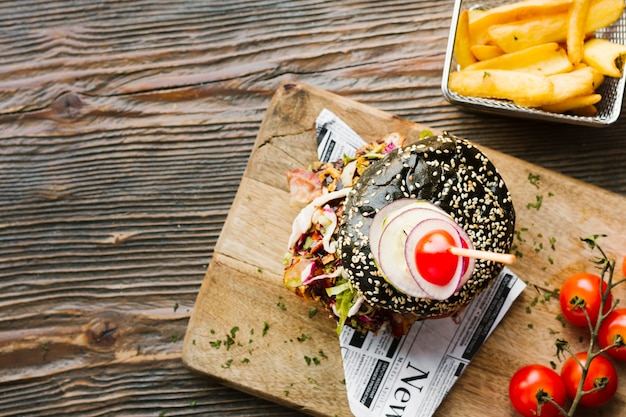 Flat-lay black burger and fries on wooden board