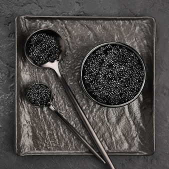 Flat lay of black caviar in bowl and spoons