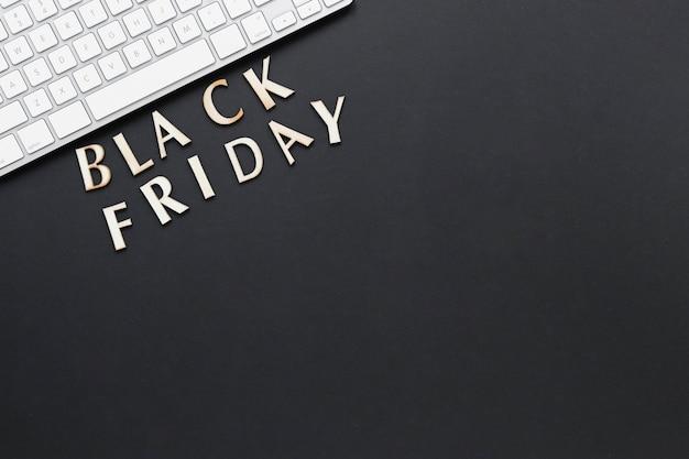 Flat lay black friday text near keyboard