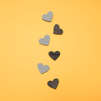 Flat lay of black and grey hearts in line on yellow bright background