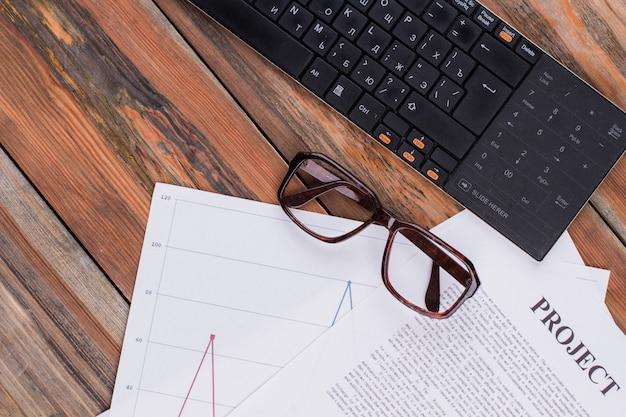 나무 테이블에 평평한 검은색 키보드 안경과 문서