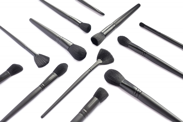 Flat lay of black makeup brushes collection isolated on white space