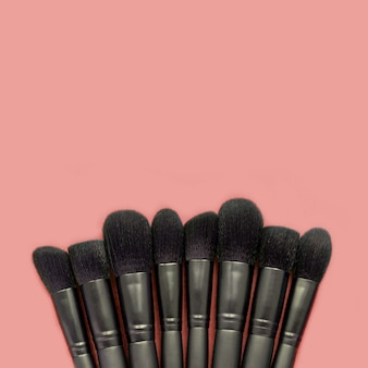Flat lay of black makeup brushes on peachy space