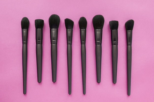 Flat lay of black makeup brushes on pink space. top view of make-up brushes set