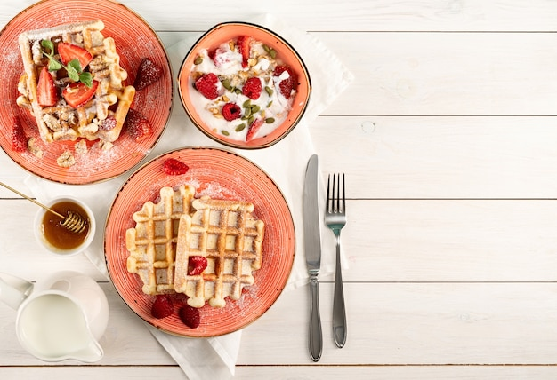 Flat lay of black plate with belgian waffles with fresh stawberry on white wooden background. flat lay, top view copy space.