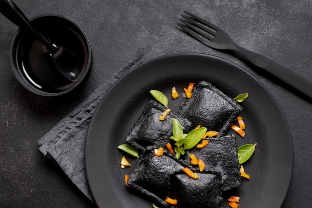Ravioli neri piatti distesi sul posto con salsa