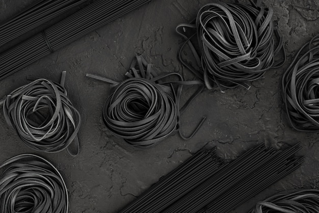 Flat lay of black tagliatelle and spaghetti