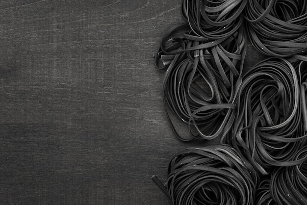 Flat lay of black tagliatelle with copy space