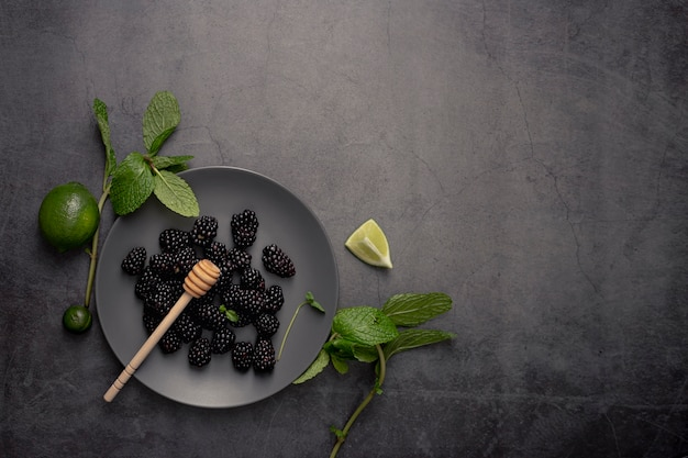 Flat lay of blackberries on plate with limes and honey dipper