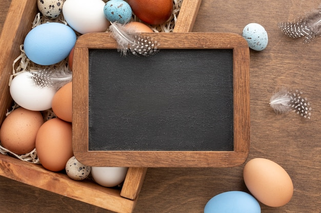 Flat lay of blackboard on top of box with eggs for easter