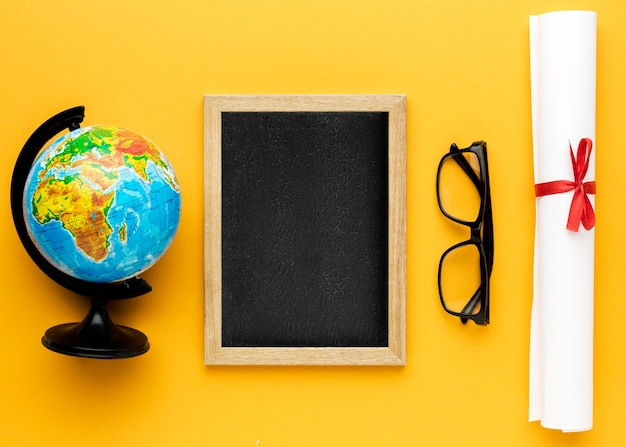 Flat lay of blackboard with academic cap and glasses