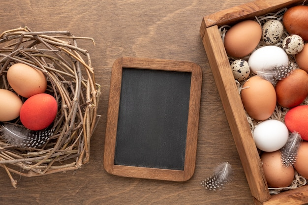 Flat lay of blackboard with next with eggs for easter
