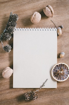 Flat lay of blank brown notebook on wooden table.