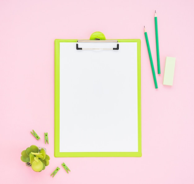 Flat lay of blank clipboard on pink background