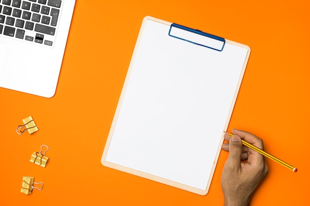 Flat lay blank clipboard with orange background