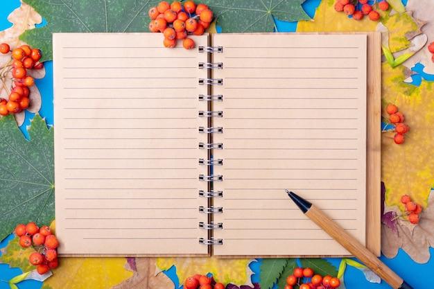 Плоские лежал пустой футляр для рукоделия и ручка на осенних опавших сухих разноцветных листьях на синем фоне. учиться в школе осенью в сентябре и концепции октября. пустой блокнот макет шаблона