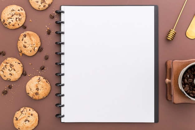 Flat lay of blank menu notebook with cookies