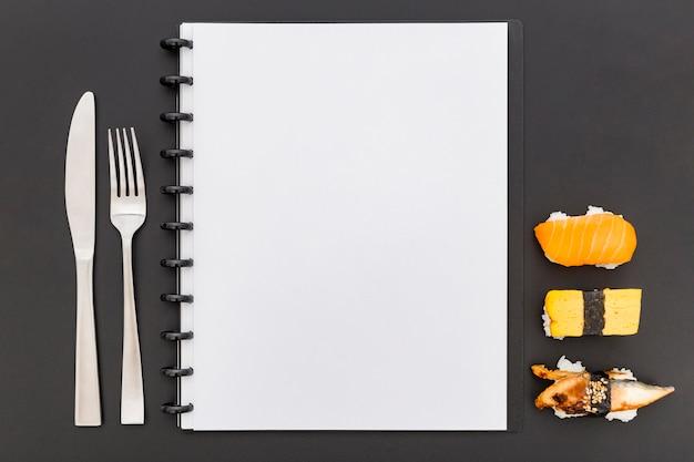 Disposizione piana del taccuino in bianco del menu con i sushi e le coltelleria