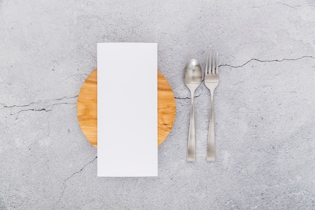Flat lay of blank menu paper on concrete with cutlery