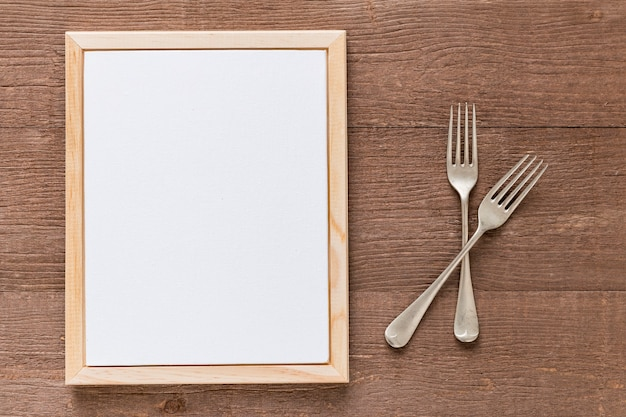 Flat lay of blank menu paper with cutlery on wooden surface