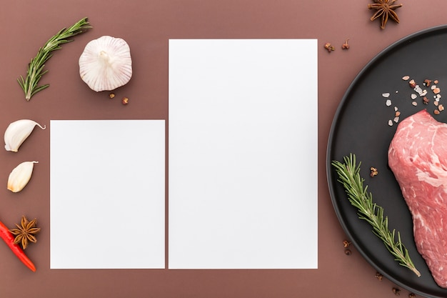 Flat lay of blank menu paper with meat on plate and garlic