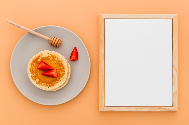 Flat lay of blank menu paper with pancakes on plate