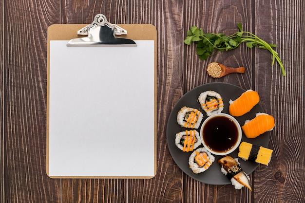 Flat lay of blank menu with sushi on wooden surface