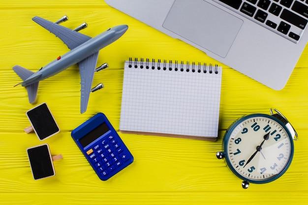 Плоский лежал пустой блокнот для копирования пространства. финансы с аксессуарами для бизнеса и путешествий на желтой древесине.
